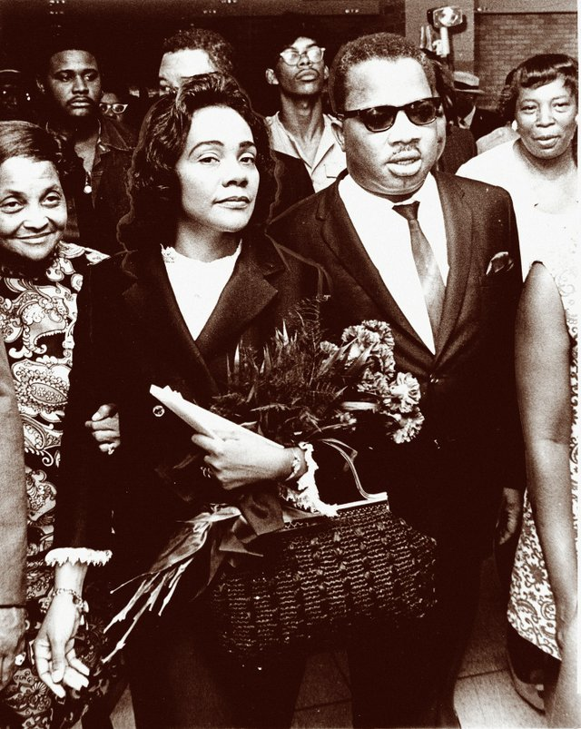 Carrying a bouquet of flowers given to her by mourners and supporters of her husband's cause, Coretta Scott King is accompanied by A.D. King, the younger brother of Dr. Martin Luther King.