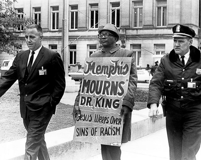 Carrying a hand-painted cardboard sign, a protestor maintains a solitary vigil outside the Courthouse in the days following King's death.