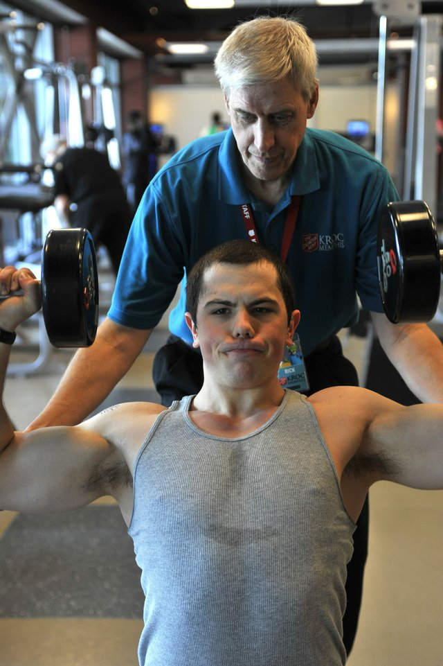 Program director Rick Ellis works with Neil Allen as he performs a dumbbell shoulder press in the fitness center, with its free weights, personal trainers, boot camp, treadmills, and more.