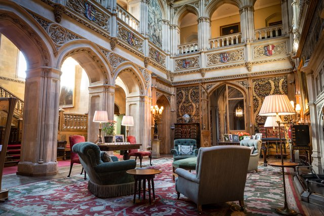 Among Highclere's most recognizable rooms is the saloon, a Gothic-style entertaining parlor paneled in 17th-century Spanish leather and featuring triple height ceilings that soar 50 feet. It is the physical and social heart of the house.