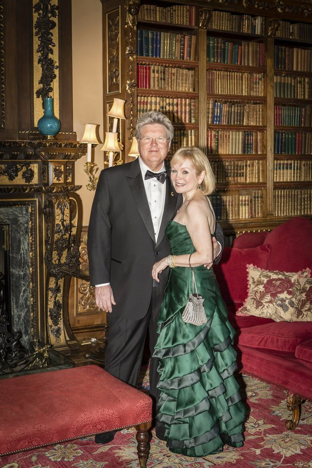 Lord Jeffrey and Lady Mary, the gracious and very glamorous hosts, who are celebrating their 40th wedding anniversary, look every bit their aristocratic parts, as they take time out to pose together in front of the library's fireplace.