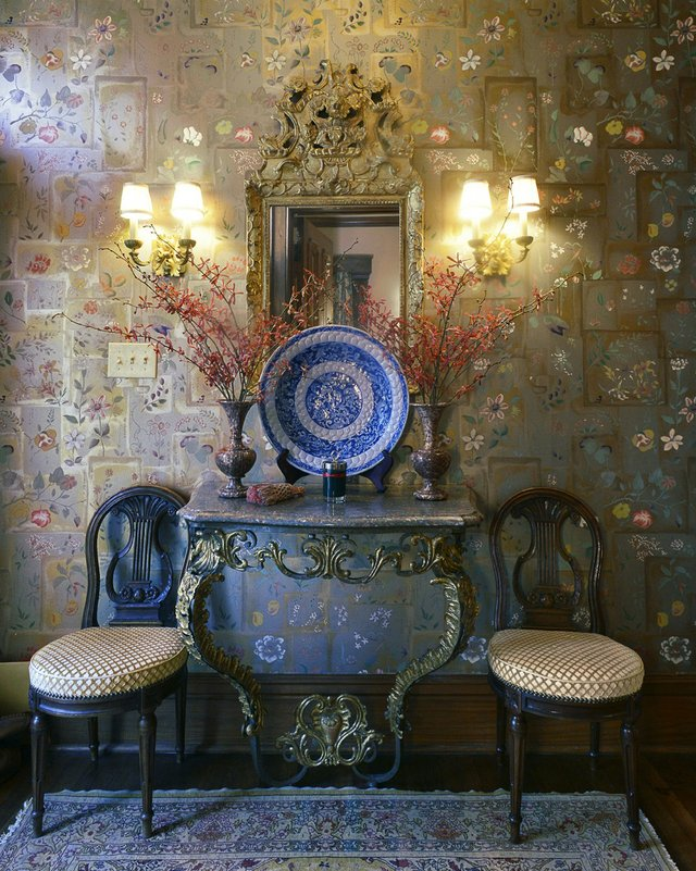 The entryway with its luminous Clarence House wallpaper welcomes visitors and sets just the right elegant tone for what lies within.