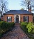 An old brick walkway lined with boxwoods leads visitors up to this historic jewel box of a house.