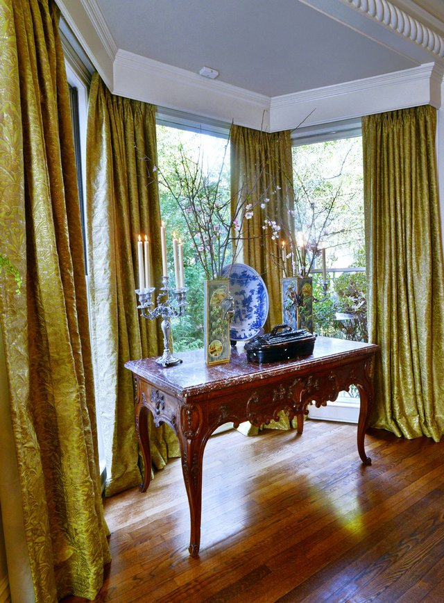 An alcove with bay window in the dining room features a Louis XV walnut console table in the center on which stands, among other objets d'art, a unique French fish tureen dating to 1840.