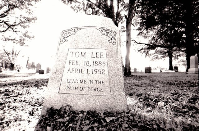 Tucked away in a shady section of Mt. Carmel Cemetery, the burial site of Tom Lee makes no mention of the Norman disaster.