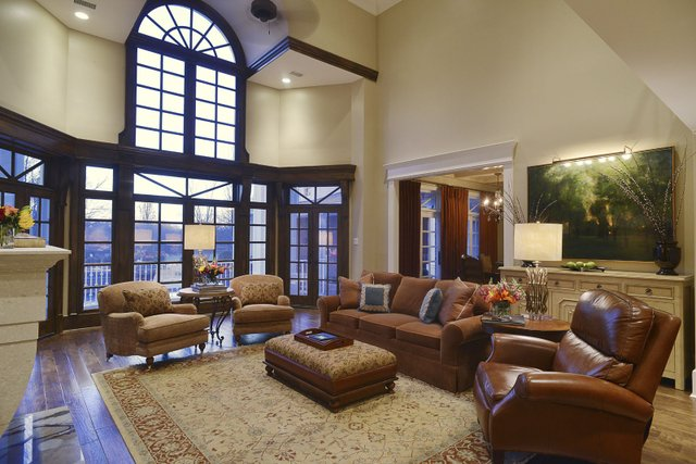 The living room with its towering ceiling, stacked stone fireplace, and wall of windows is the comfortable heart of the home.