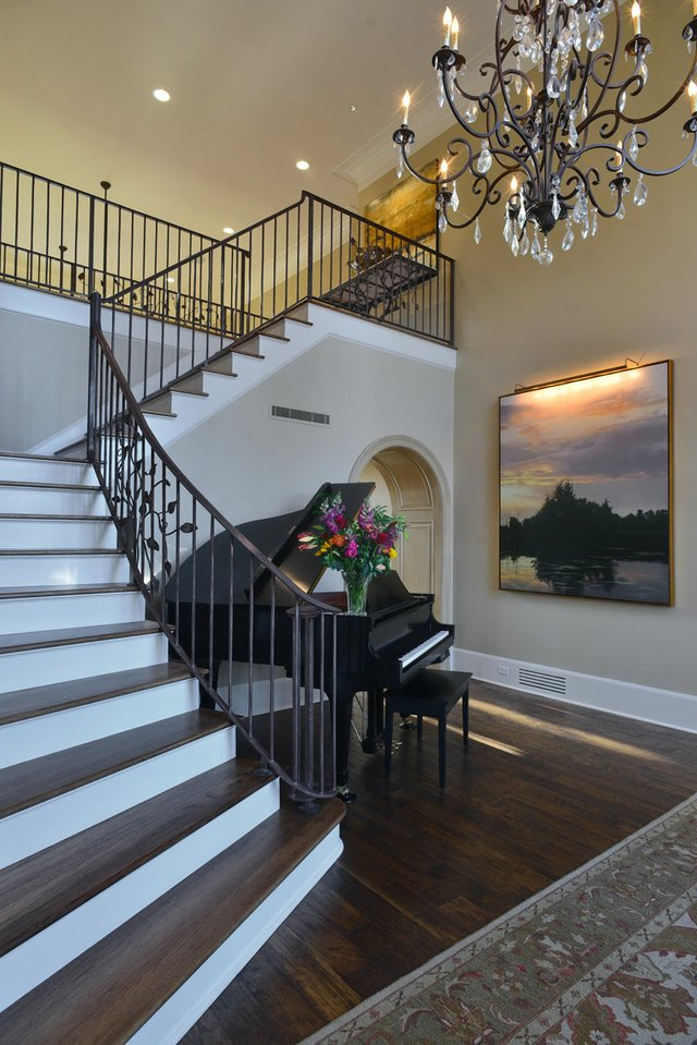 The chandelier in the entrance hall provides an elegant welcome to the home, and the leaf motif on the wrought-iron banister is in perfect keeping with the home's rural setting in eastern Shelby County.