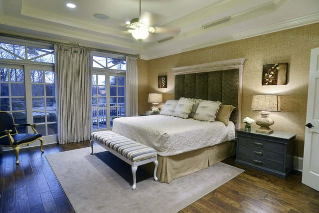 The master bedroom is papered with metallic grasscloth, which gives a glow to the room; the drapes soften the decor and afford a bit of privacy.