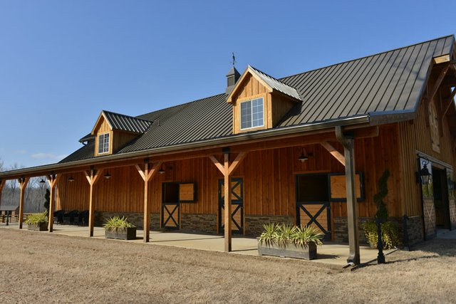 """Designer Ami Austin says, """"You could eat off the floor"""" of these handsome stables built by the Malones."""