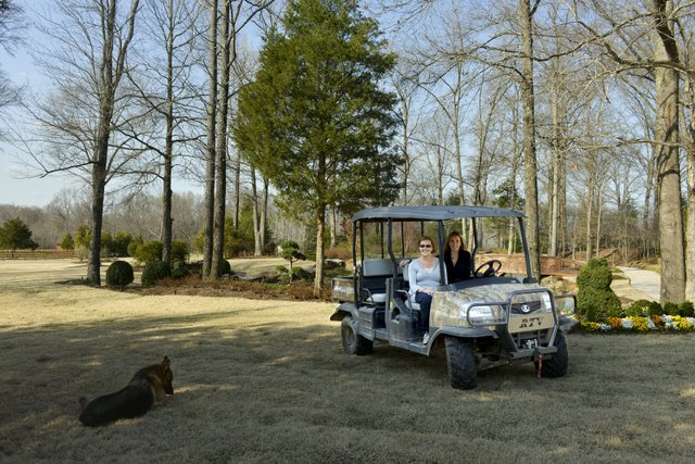 Marcia Malone (left), with her top-notch designer Ami Austin, poses on one of several all-terrain vehicles used to traverse the extensive property.