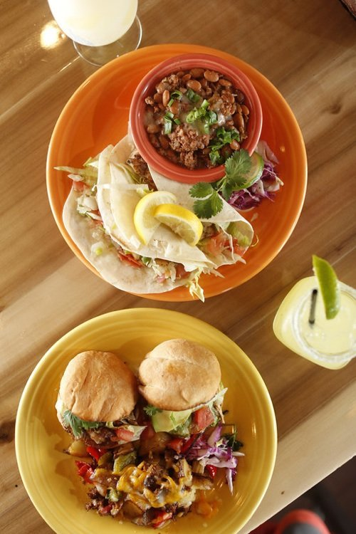Popular dishes at Cafe Ole include fish tacos and carnitas tortas layered with roast pork, avocado, and chile del arbol sauce on Mexican rolls called bolillos.