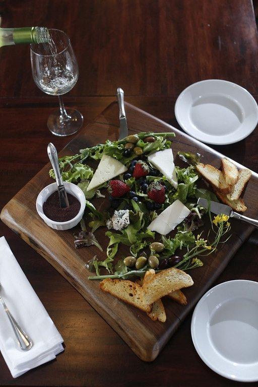 The cheese plate at Ecco on Overton Park is a pretty dish served with crusty bread, seasonal berries, and broccoli rabe.