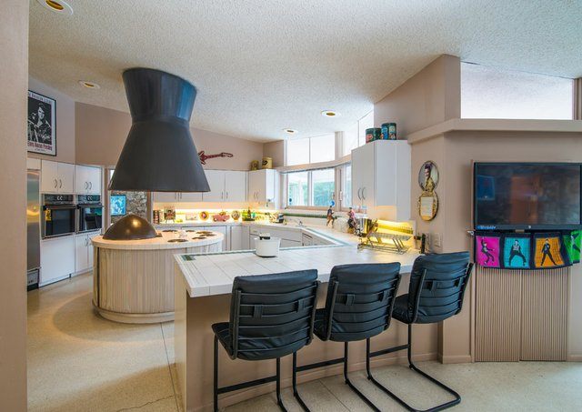 The home's stylish cream-colored round kitchen is punctuated with charcoal stools.