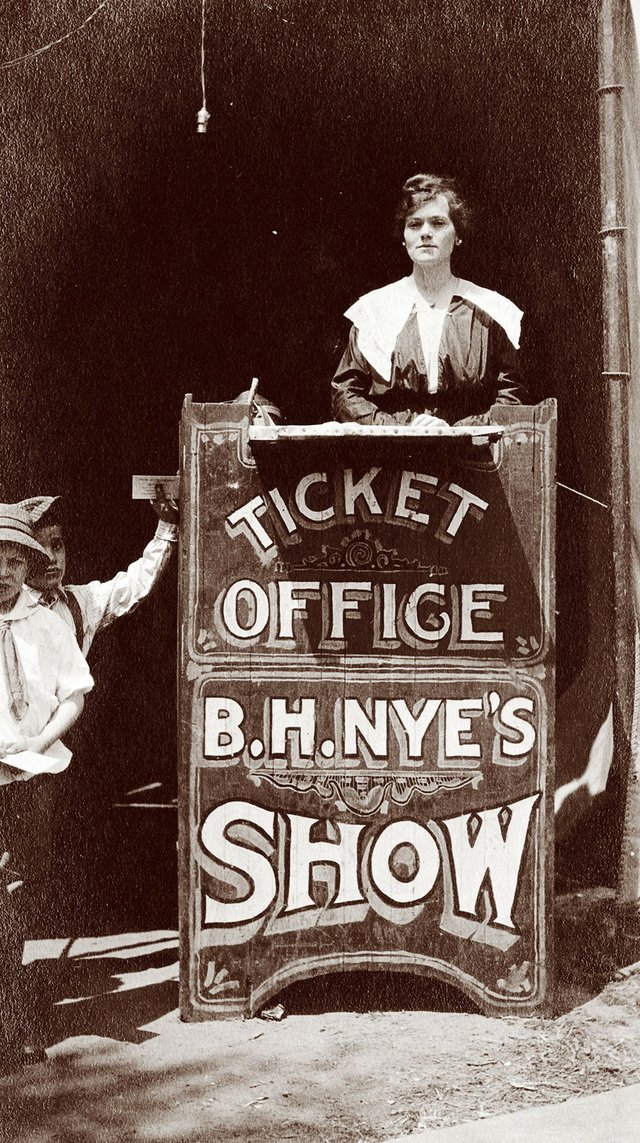 """The woman in this 1912 photo, identified as Anna Bennett, is working the """"ticket office"""" for B.H. Nye's Show — a traveling carnival at East End Park."""