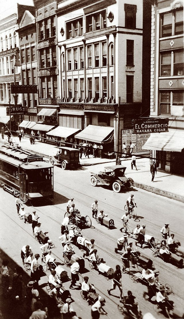 A parade of soapbox derby cars, pushed from behind, makes its way down Main Street in front of a trolley.