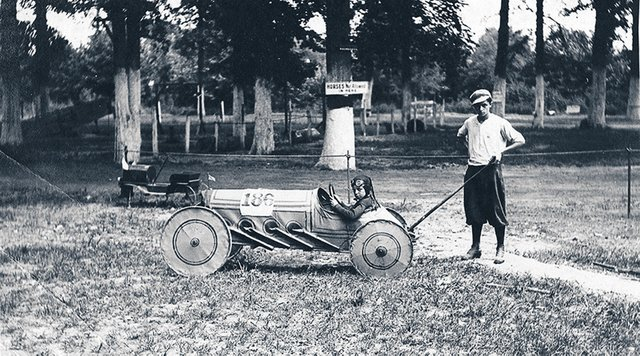 Two boys pose with their racing-styled soapbox derby car, complete with fake exhaust pipes.