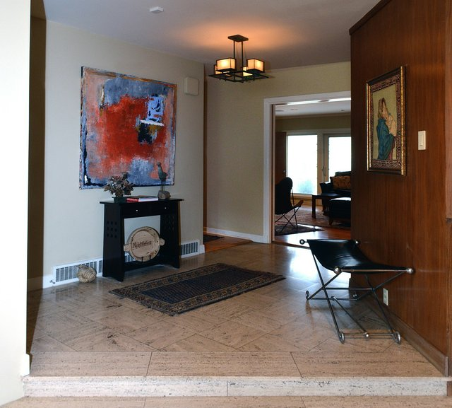 The wide entrance foyer is light and bright and minimally furnished with a small console table.