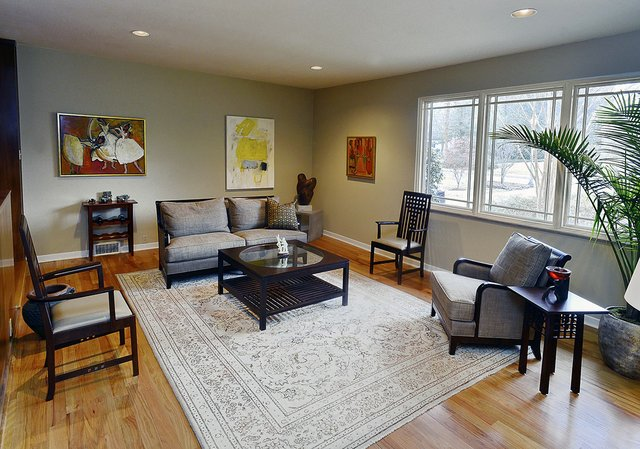 The loveseat, coffee table, and comfortable chair seem to float in the formal living room, which is anchored by a handsome, inherited neutral-toned oriental.