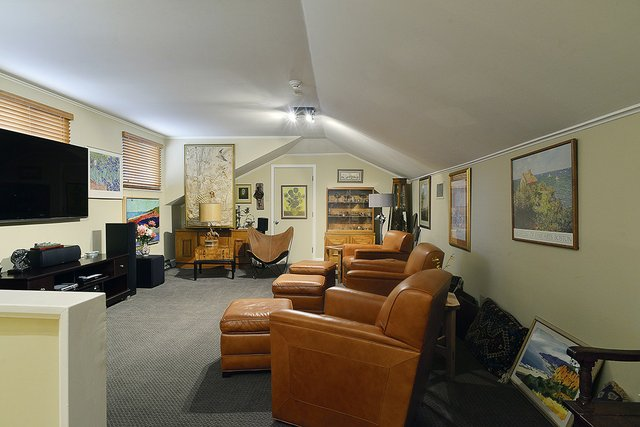 "The comfortable Malibu ""man cave"" media room upstairs features a large-screen TV and four leather swivel Stickley chairs."