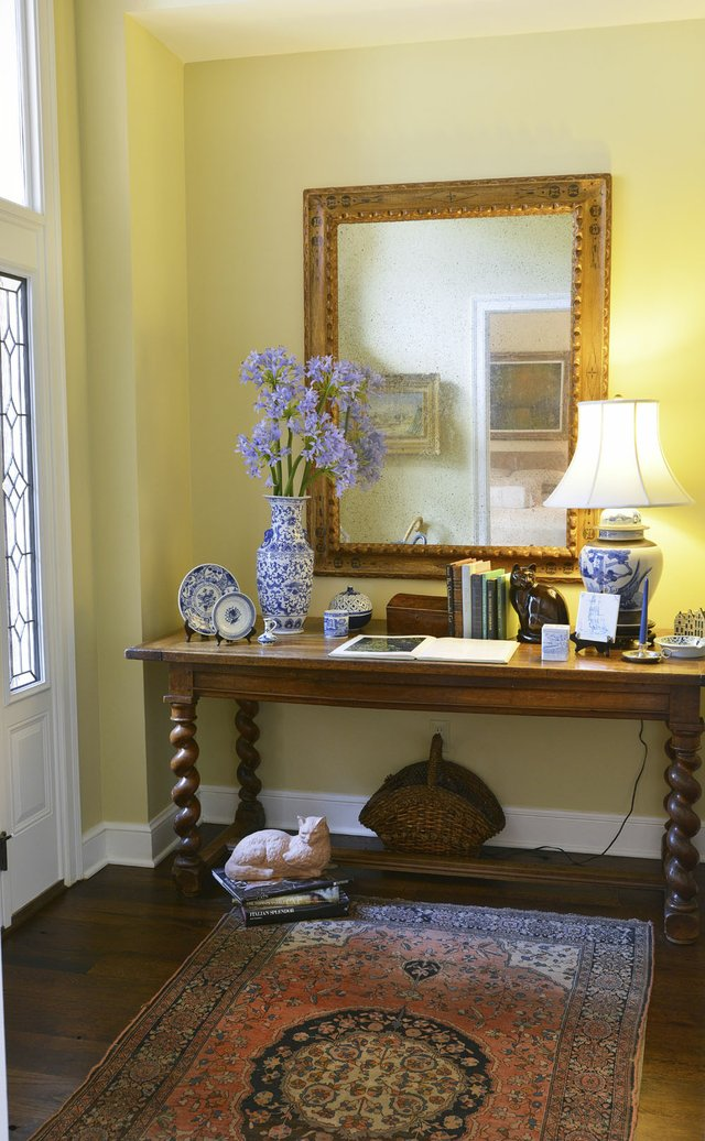 A blue and yellow color scheme and an oriental rug in the home's elegant entryway offer visitors a warm welcome.
