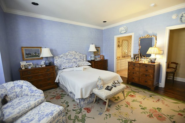 Blue and white toile and a flower-sprigged carpet decorate the master bedroom, which is entered off a little hall especially designed by Cannon.