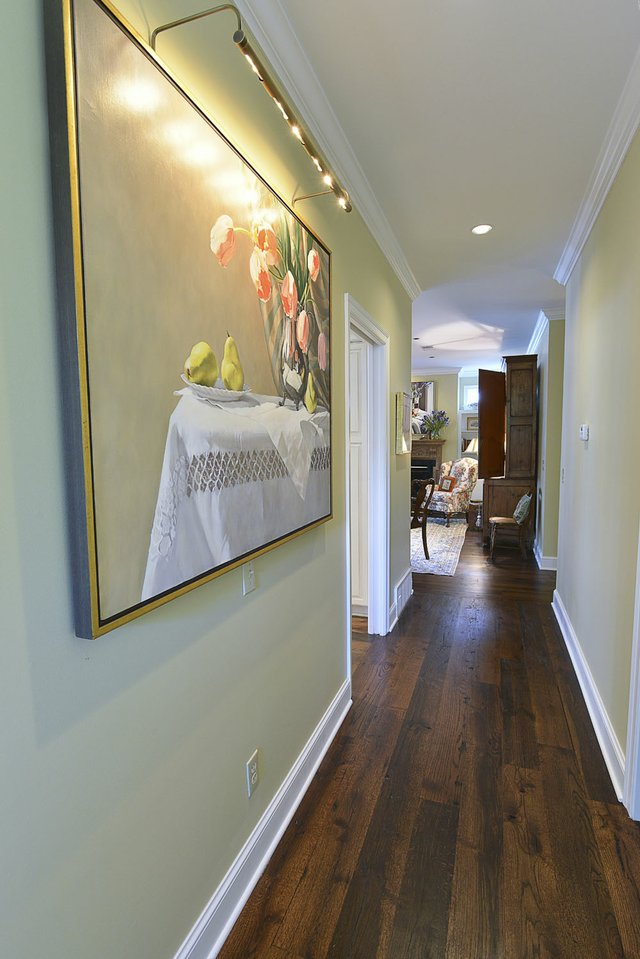 The long, central hall of the couple's home, with its large, luminous painting and lustrous hardwood floors, connects the house's downstairs rooms.