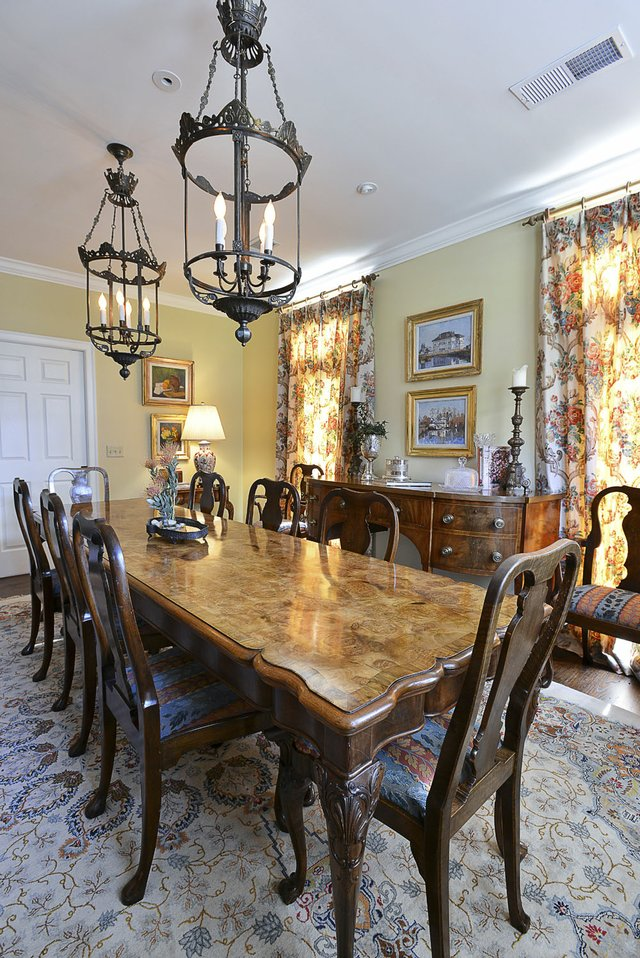 A handsome antique table and massive lantern light fixtures anchor the dining room, which opens onto the living room, a configuration that allows for casual living and comfortable entertaining.