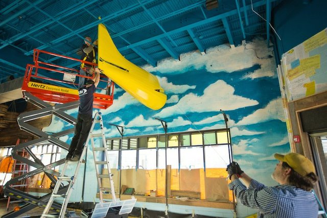 Workers install one half of a one-seater airplane, transformed as a crop duster with yellow paint, inside soon-to-open Belly Acres designed by Memphis-based Glennys Cowles Designs.