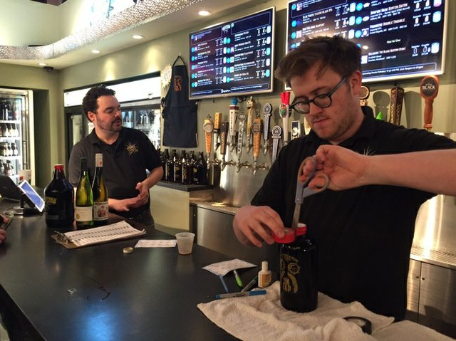 Andrew Woods caps a 32-ounce squealer filled with Acrobat Pinot Noir from Oregon at Joe's new growler station in Midtown, where customers can taste before they buy.