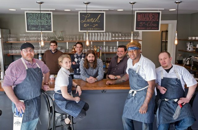 Andrew Ticer and Michael Hudman, center, with the staff at their new restaurant and butcher shop  called Porcellino's. Small plates from Porcellino's are pictured below.