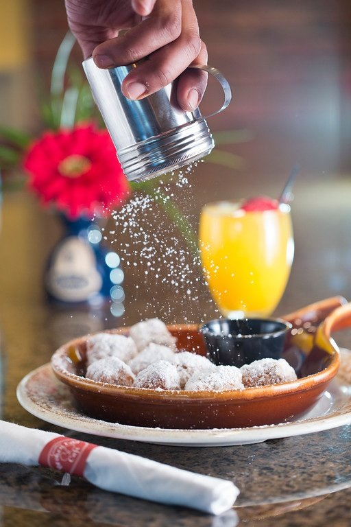 Popular dishes include biscuit beignets dusted with powdered sugar, above, and an array of eggs and pancakes served in the photo below by Howard Boxley.