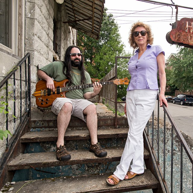 Jamie and Leigh Davis relax on the front porch of the old hotel that has served as their home.