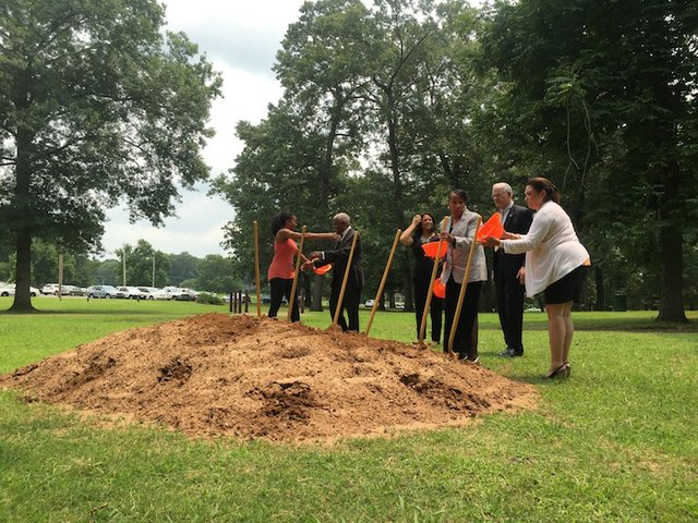 A crowd of local leaders breaks ground on a new adult fitness station in Audubon Park.