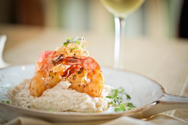 Chef Derek Smith at the Capriccio Grill plates grilled shrimp garnished with micro-greens on a creamy mound of stoneground grits.